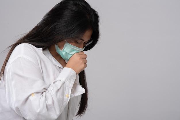 Симптом простуды или аллергии при гриппе. больная молодая азиатская женщина чихает в изоляте маски на сером цвете.