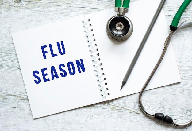 Flu season은 청진기 옆 나무 탁자 위의 공책에 쓰여 있습니다.