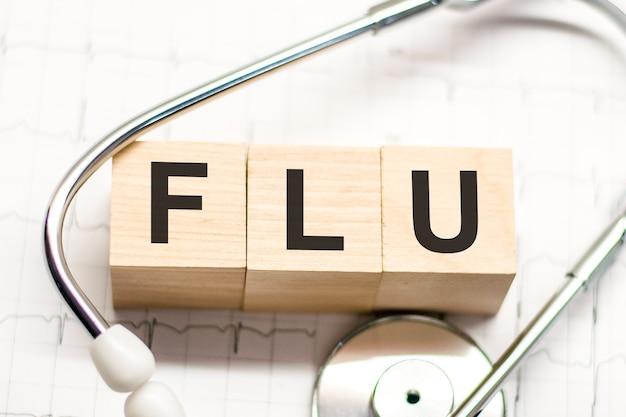 밝은 배경에 나무 블록과 청진기에 쓰여진 독감 단어. 병원, 진료소 및 의료 사업에 대한 의료 개념