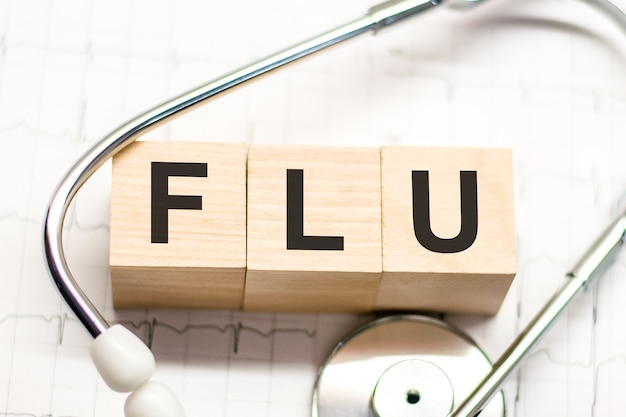Flu word written on wooden blocks and stethoscope on light background. healthcare conceptual for hospital, clinic and medical busines