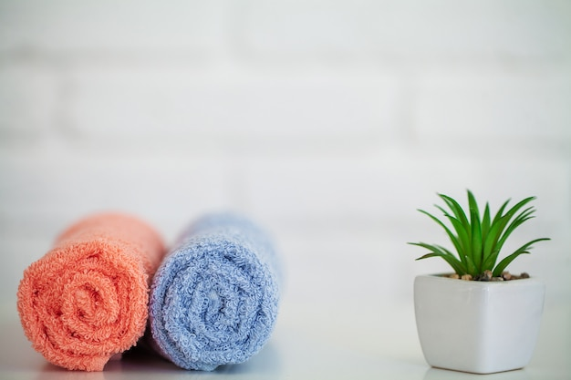 Fluffy bath towels on light wooden table with decor