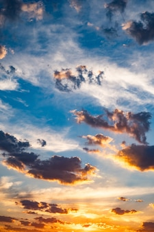 空にはふわふわ青い雲とオレンジ色の夕陽が沈む Premium写真