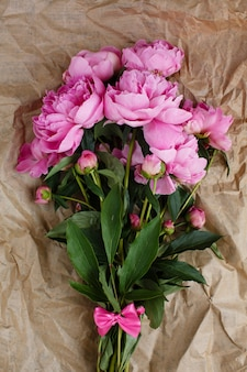 Fluffy bouquet of pink peonies flowers in sunlight on wrinkled craft paper surface, top view,