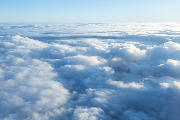 Fluffy clouds seen from above from the airplane window. climatology and weather concept.
