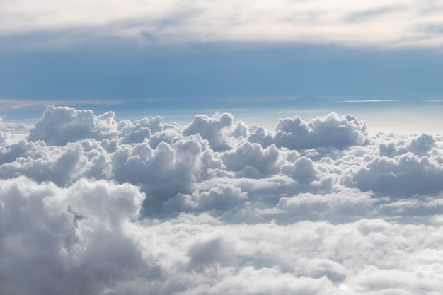 Above fluffy clouds with blue sky from airplane