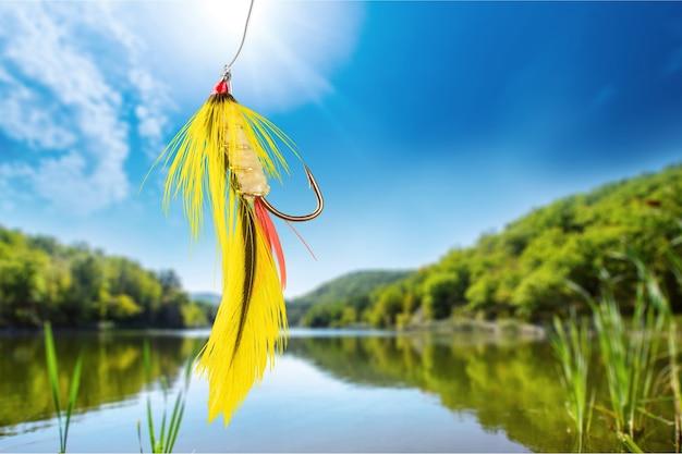 Пушистый крючок для ловли рыбы нахлыстом на фоне