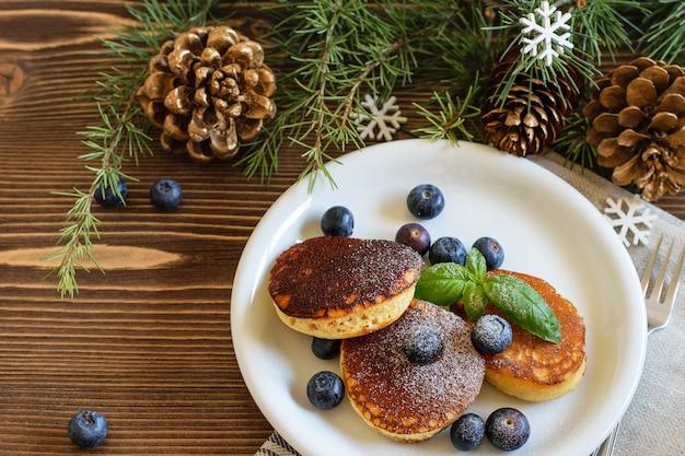 Пушистые японские блинчики с черникой, посыпанные сахарной пудрой на белой тарелке. новогодний фон, вид сверху. концепция здорового питания.