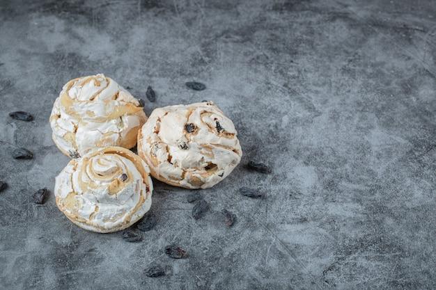 Soffici muffin alla meringa con uva secca nera sul tavolo.
