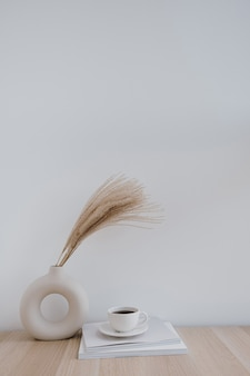 Fluffy pampas grass  reed in stylish vase, coffee cup and magazines against white wall