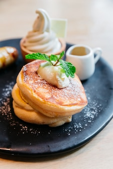 Fluffy pancakes served with caramel banana, ice cream and syrup.