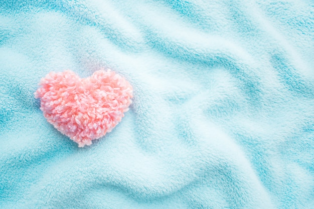 Fluffy pink thread heart on blue soft cozy fabric background