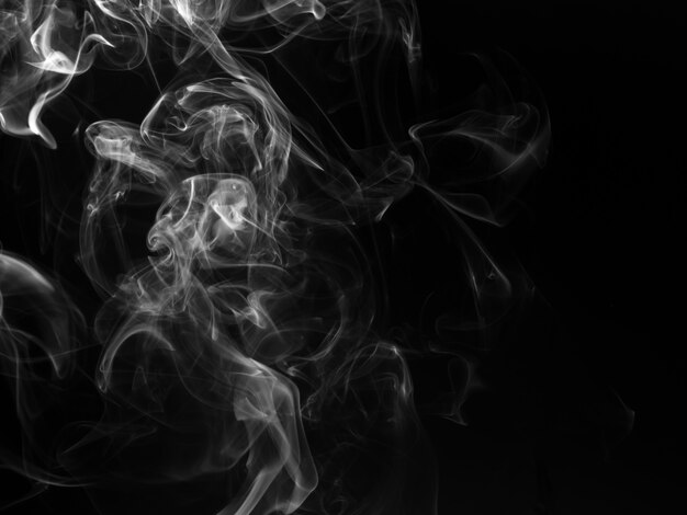 Fluffy puffs of white smoke and fog on black background, fire  and darkness concept