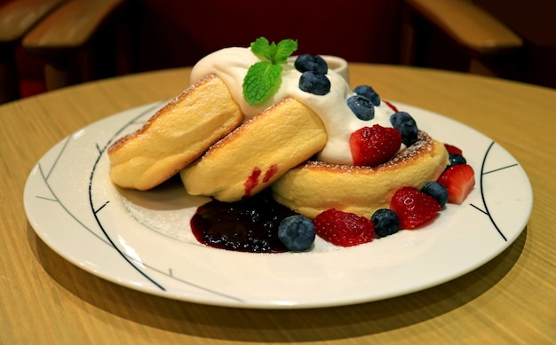 Fluffy souffle pancakes with fresh mix berries and mascarpone cream served on round wooden table