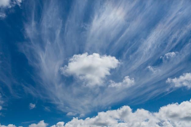 青い空を横切るふわふわの白い雲。スペースをコピーします。