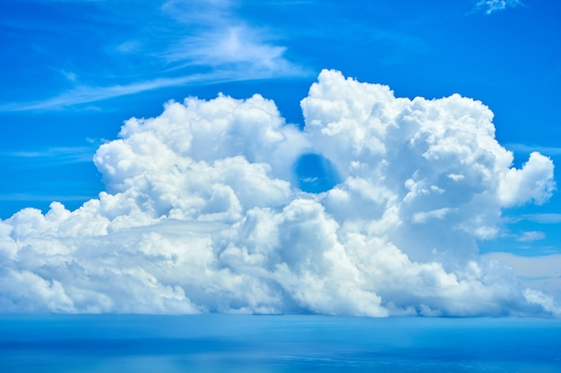 Fluffy white clouds over blue ocean water.
