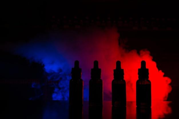 Жидкость для электронных сигарет на фоне цветного облака дыма