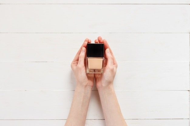 Fluid foundation with makeup product in woman hands.