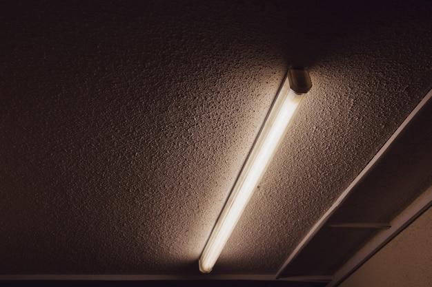 アパートの住宅の天井に蛍光灯。大きな建物のセメント天井と蛍光灯。碑文やロゴのあるクリエイティブの背景。コピースペース