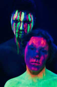 Fluorescent make-up on woman and man face