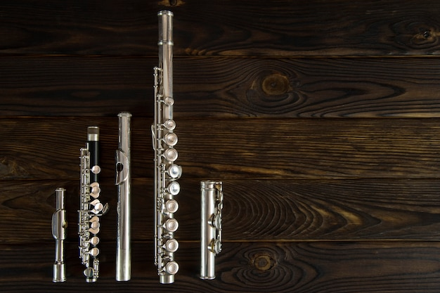 Детали флейты, выложенные на деревянной поверхности