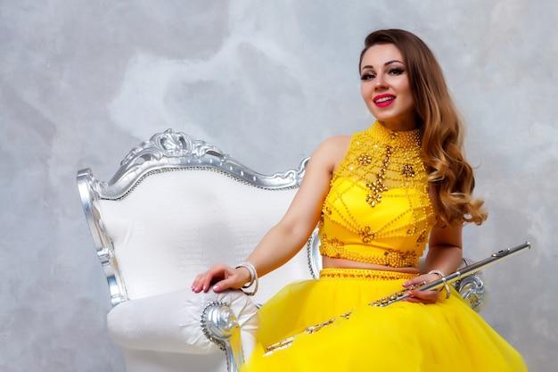 Флейтист с флейтовым инструментом. красивая актриса в желтом платье с золотыми волосами красоты на стуле. милая молодая женщина с флейтой. классический женский музыкант на фоне стены текстуры. копировать пространство