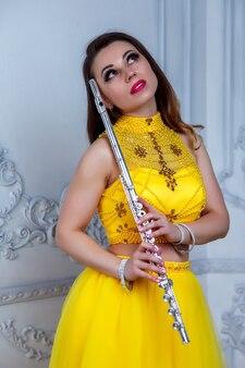 Флейтист с флейтовым инструментом. симпатичная актриса в желтом платье с красотой золотистых волос остается в комнате. милая молодая женщина с флейтой. классический женский музыкант на фоне стены текстуры. копировать пространство