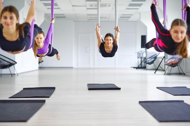 Fly антигравитационная йога, женские групповые тренировки с гамаками. фитнес, пилатес и танцевальные упражнения смешивают. женщины на тренировке йоги в спортивном клубе
