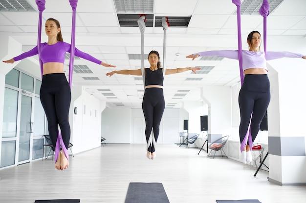 Fly антигравитационная йога, женские групповые тренировки с гамаками. фитнес, пилатес и танцевальные упражнения смешивают. женщины на тренировке йоги в спортивной студии