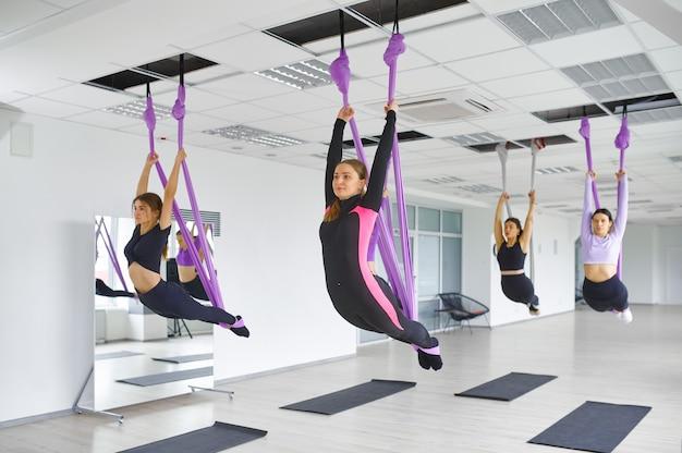 Fly антигравитационная йога, женские групповые тренировки с гамаками. фитнес, пилатес и танцевальные упражнения смешивают. женщины на тренировке по йоге