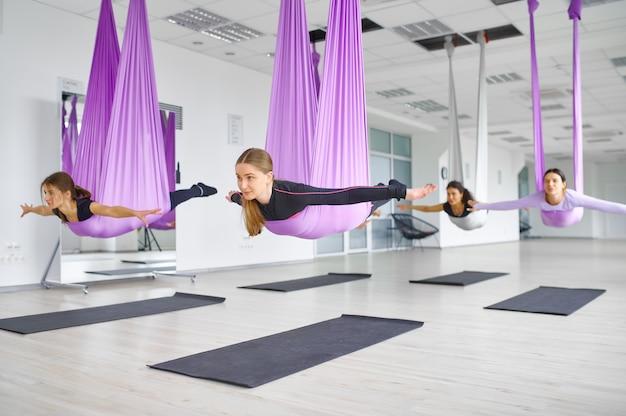 Флай антигравитационная йога, групповые занятия с гамаками. фитнес, пилатес и танцевальные упражнения смешивают. женщины на тренировке по йоге