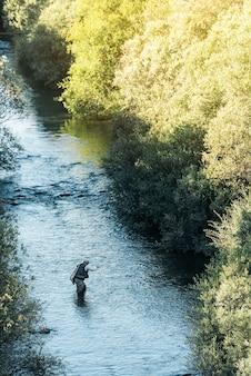 아름다운 강에서 플라이 낚시대를 사용하는 플라이 어부