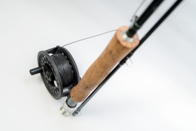 Fly fishing fly on the rod on white background. reel and vintage salmon flies