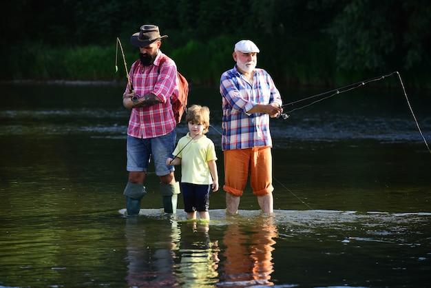息子と孫の釣りをするマスの年配の男性のためのフライフィッシングは人気のあるレクリエーションになりました...