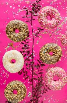 핑크색 표면에 토핑을 얹은 에어 체리와 초콜릿 도넛으로 날아보세요.