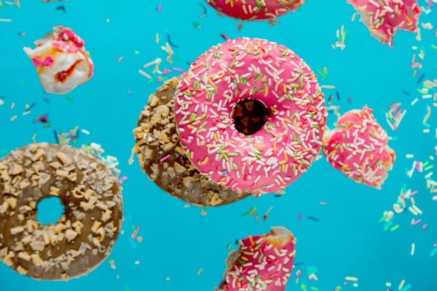파란색 표면에 토핑과 함께 에어 체리 도넛으로 날아갑니다.