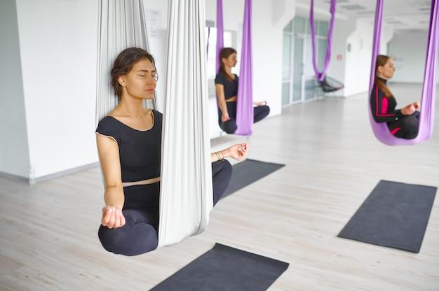 フライまたはエアロヨガ、グループトレーニング、ハンモックにぶら下がっています。フィットネス、ピラティス、ダンスエクササイズがミックスされています。ジムでのヨギトレーニングの女性、ライフスタイルに合う