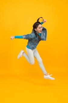 너무 높이 날아. 진짜 재미 있는 아이. 스포츠에서의 성공. 행복한 승자 아이. 노란색 배경에 십 대 소녀 점프입니다. 이것은 완전한 승리입니다. 성공을 향해 달린다. 어린 시절 행복의 개념입니다.