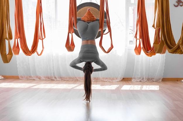 Fly йога красивая женщина висит вверх ногами позу лотоса широкий угол
