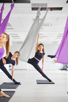 Занятия флай-йогой, женские групповые тренировки, подвешивание на гамаках. фитнес, пилатес и танцевальные упражнения смешивают. женщины на тренировке йоги в спортивной студии