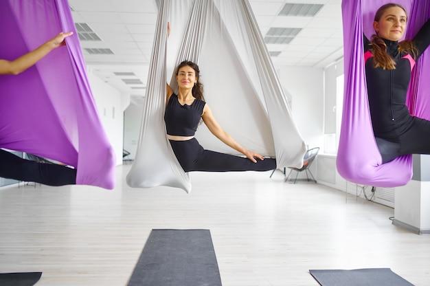 Флай-йога, женские групповые тренировки, подвешивание на гамаках. фитнес, пилатес и танцевальные упражнения смешивают. женщины на тренировке по йоге