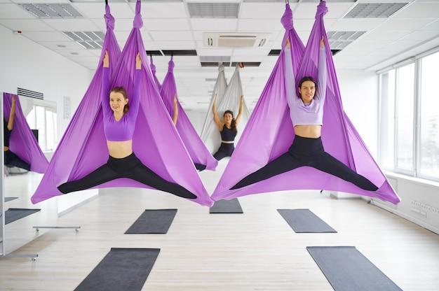 Флай-йога, женские групповые тренировки, подвешивание на гамаках. фитнес, пилатес и танцевальные упражнения смешивают. женщины на тренировке йоги в спортивной студии