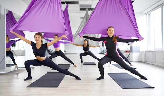 Флай-йога, женские групповые тренировки с гамаками. фитнес, пилатес и танцевальные упражнения смешивают. женщины на тренировке йоги в спортивной студии