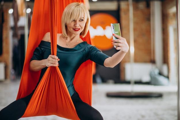 Vola istruttore femminile di yoga in palestra