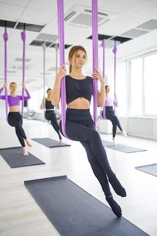 Флай-йога, групповые занятия с гамаками. фитнес, пилатес и танцевальные упражнения смешивают. женщины на тренировке йоги в спортивной студии