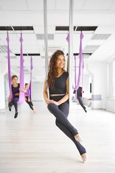 Студия флай-йоги, женские групповые тренировки, подвешивание на гамаках, антигравитация. фитнес, пилатес и танцевальные упражнения смешивают. женщины на тренировке йоги в тренажерном зале