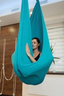 Женщина медитации в гамаке. fly йога упражнения на растяжку в тренажерном зале