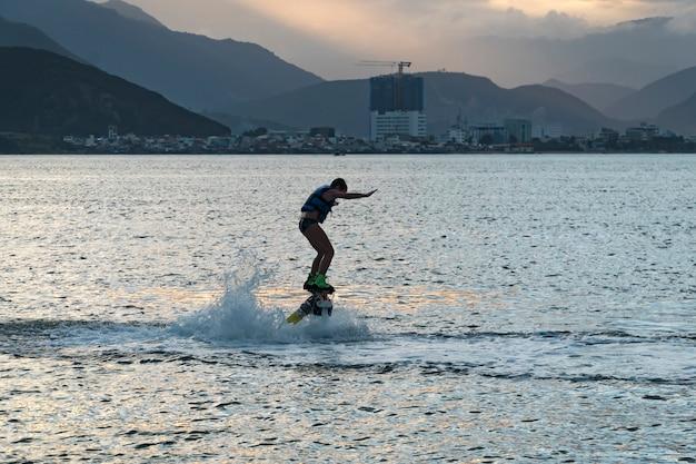 Флайборд. воздух самый дальний полет на ховерборде. мальчик летит на борту. flyboard - это воздушная машина для гидроциклов, позволяющая двигаться под водой. ребенок веселится на море.