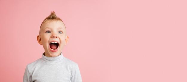 전단. 분홍색 벽에 고립 된 행복 한 소년입니다. 행복하고 쾌활 해 보입니다. copyspace 어린 시절, 교육, 감정, 표정 개념. 높이 뛰고 즐겁게 놀기