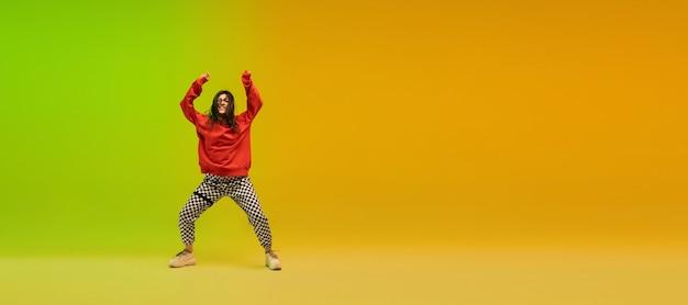 チラシ。ネオンの光のダンスホールでカラフルなスタイリッシュな服を着てヒップホップを踊るスタイリッシュなスポーティーな女の子。