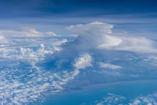 シンガポールの領土で地球と雲の上を飛んでいます。飛行機のウィンドウビュー。飛行機は地球の上空を飛んでいます。